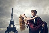 Elegant young lover holding her lover with the Eiffel Tower in the background