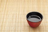 Japanese cup of tea on a bamboo mat - a traditional cast iron red hobnail design with black enamel i