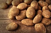 stock photo of vegan  - Fresh potatoes on rustic wooden background - JPG