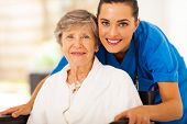 stock photo of scrubs  - happy senior woman on wheelchair with caregiver - JPG
