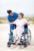 caregiver talking to disabled senior woman outdoors