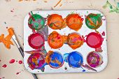 Messy array of colors of children's paint in a tray with a paint brush.