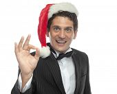young handsome caucasian man in black dinner jacket looking at camera smiling santa's hat finger han