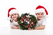Kids with traditional advent wreath wearing santa hats