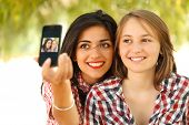 stock photo of two women taking cell phone  - Two girl with smartphone taking a self portrait