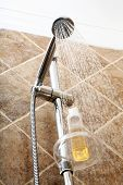 Silver chromed shower head in a bathroom with running water