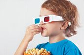 Young ironic boy in 3D glasses eating popcorn