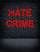 image of racial discrimination  - Hate crime social problem concept with a dark grey brick wall with spray can paint painted on the building structure as a symbol of racism and race discrimination as an illegal racial act of hatred and vandalism based on fear and xenophobia - JPG