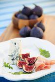 Italian antipasto figs with prosciutto, gorgonzola cheese and rucola