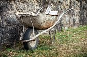 Old Construction Wheelbarrow Stands Against The Wall