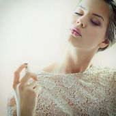 Girl with perfume, young beautiful woman holding bottle of perfume and smelling aroma, toned soft beige and noise added