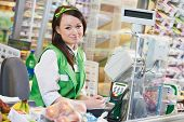 stock photo of supermarket  - Portrait of Sales assistant or cashdesk worker in supermarket store - JPG