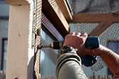 foto of hammer drill  - A carpenter is building a wooden door gate - JPG