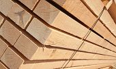 image of lumber  - Stack of new wooden studs at the lumber yard - JPG
