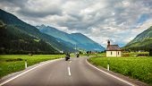Bikers on mountainous highway, Europe, Austria, Alps, road along little village, driving motorcycle,