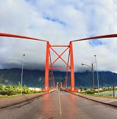 Patagonia, Chile. Red bridge over the fjord. A gorgeous summer day and a huge cloud. The picture was taken Fisheye lens