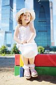 Little cute girl with white bag sits on sandbox near skyscrapers at sunny day.