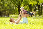 Cute little baby in summer  park with mother  on the grass. Sweet baby and mom  outdoors. Smiling em