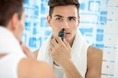 pic of electric trimmer  - handsome young man remove hair from his nose with trimmer - JPG