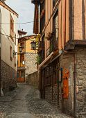 The narrow street with old houses in Potes, Cantabria, Spain.