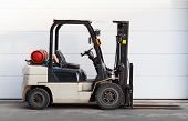 picture of lift truck  - Standard small gas engine truck lift above gray storage gate - JPG