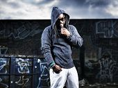 stock photo of rapper  - man in hoodie in front of graffiti - JPG