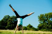 Woman Doing Cartwheel In A Field
