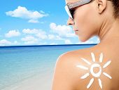 stock photo of sunbathing woman  - Rear view image of a woman with sunscreen lotion - JPG
