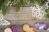 stock photo of gingerbread man  - Christmas fir tree and decor covered with snow on wooden board background - JPG