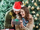 Happy young couple holding present against Christmas tree in store