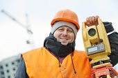 surveyor worker portrait with theodolite transit equipment at road construction site outdoors