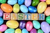 The word Easter spelled out in childrens toy blocks surrounded by a group of colorful plastic eggs.