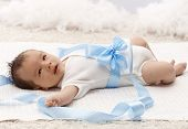 Lovely newborn baby lying on back in white bodysuit and blue ribbon around waist.
