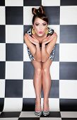 Attractive surprised young woman wearing stripy high heels on checkered background