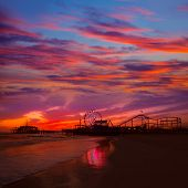 stock photo of nightfall  - Santa Monica California sunset on Pier Ferris wheel and reflection on beach wet sand - JPG