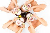 foto of facial  - A picture of four friends enjoying their time in spa with facial masks over white background - JPG