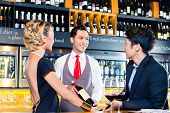 Asian couple tasting red wine in wine shop