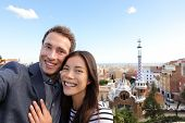 Happy travel couple in Park Guell, Barcelona, Spain. Beautiful young multiracial couple looking at camera taking selfie smiling happy having fun on Europe vacation trip. Asian woman, Caucasian man.
