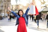 Shopping woman happy on La Rambla street Barcelona. Shopper girl holding shopping bags up excited ou