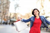 Shopping girl happy shopping outside. Beautiful woman running joyful with shopping bags outdoors wea
