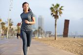 Running woman jogging on Barcelona Beach, Barceloneta. Healthy lifestyle girl runner training outsid