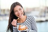 Waffles - woman eating waffle happy outdoors smiling laughing looking at camera. Beautiful girl eati