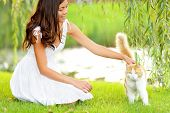 Woman petting cat in summer park. Happy cute girl playing with adorable cats in city park during spring or summer. Beautiful mixed race Asian Caucasian female model smiling happy outdoors.