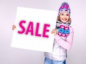 foto of outerwear  - Adult smiling woman in winter outerwear holds the white banner with sale word on it - JPG