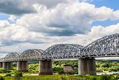 steel arch railroad bridge across the river on background sky with cloud