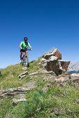 Mountain Biker Riding Downhill In Swiss Alps