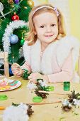 Smiling little girl dressed in furry mantle sits at wooden table and paints revealed pine-cone with green gouache