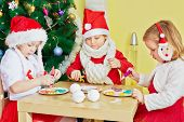 Three children play in food sitting at table in room with decorated christmas tree