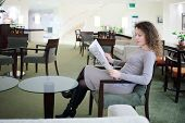 Pretty woman in dress sits at table in hall and reads newspaper