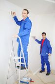 Two men in blue, pasting paint fiberglass and painting wall in new apartment